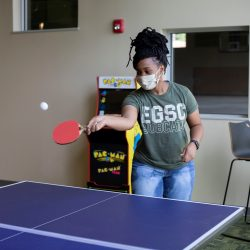 Student playing ping pong with EGSC shirt